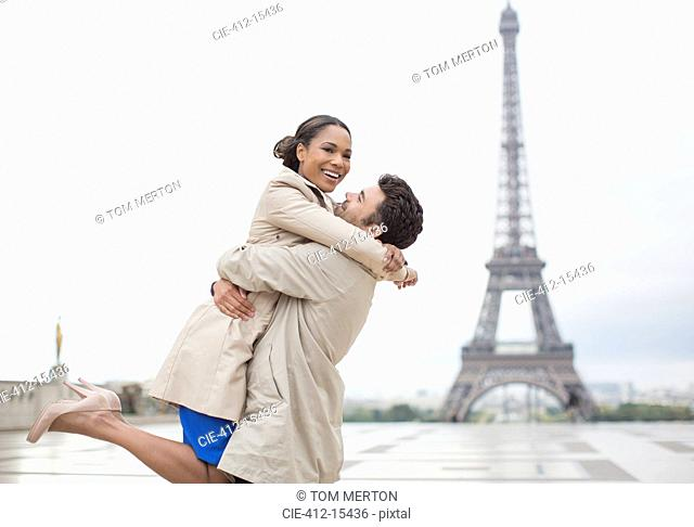 Couple hugging by Eiffel Tower, Paris, France