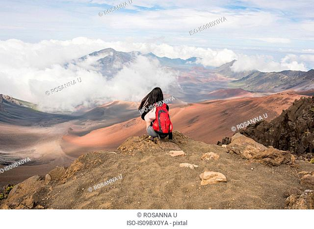 Hiker on edge of mountain top, Haleakala National Park, Maui, Hawaii