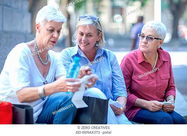 Senior and mature women checking shopping receipt in city