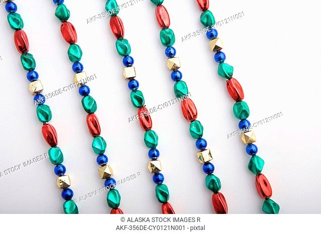 Five colorful shiny Christmas tree bead strands displayed on white background studio portrait