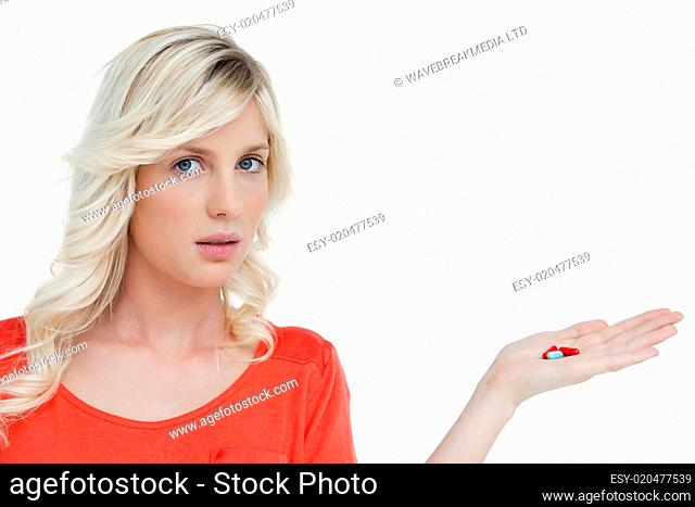 Woman looking at the camera while holding vitamins in her hand