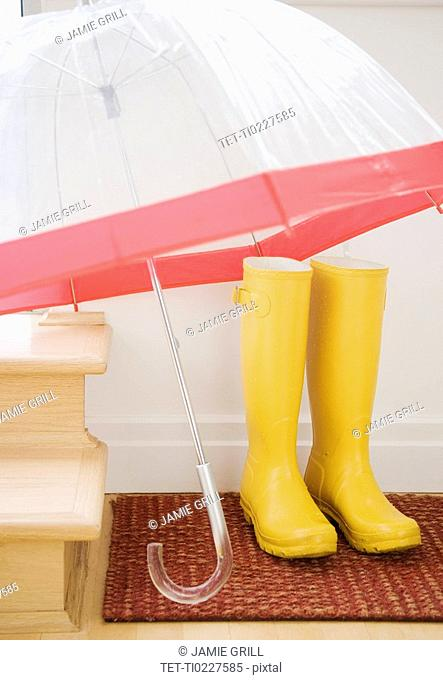 Rain boots and umbrella drying indoors