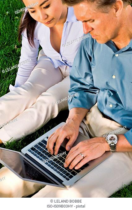 Business man and woman sitting outdoors on grass, using laptop