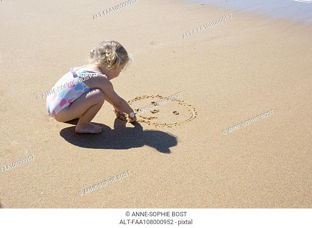 Little girl drawing smiley face in sand