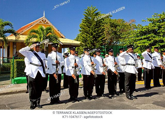 A street parade with marching band and uniformed officers in Roseau, dominica, West Indies