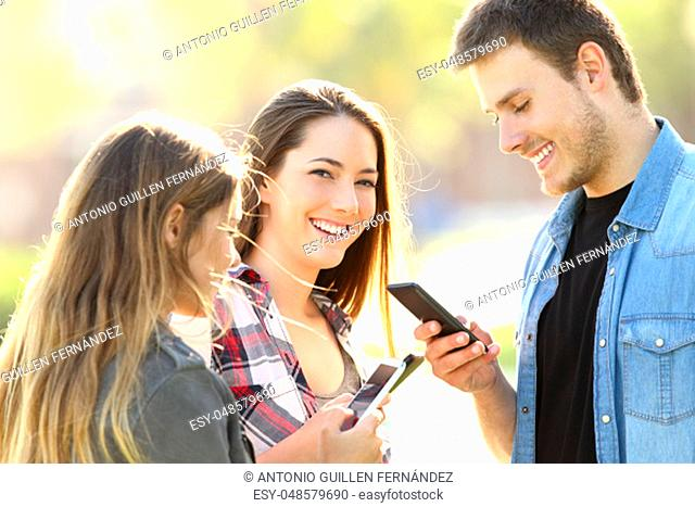 Three teens using their smart phones and one of them looking at you in the street