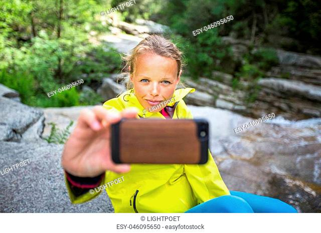 Pretty, young female hiker taking a selfie while outdoors on a hike, taking a break near a mountain stream (shallow DOF)