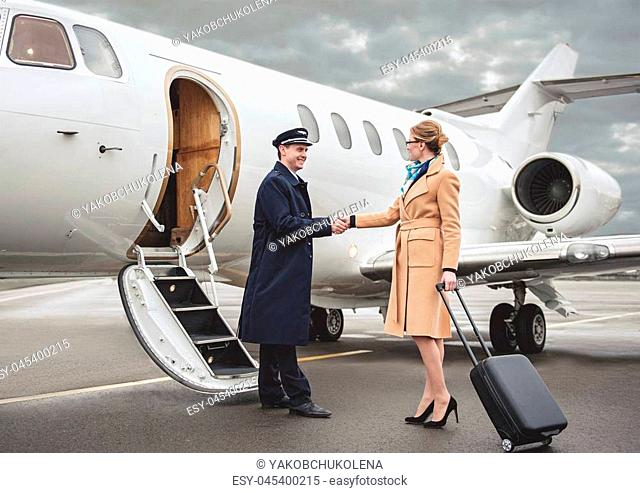 Full length outgoing businesswoman welcoming with glad pilot at airfield. Career concept
