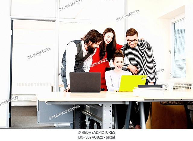 Colleagues using laptop at desk