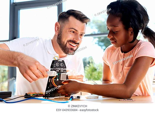Playful mood. Handsome smiling young man holding the arms of a black cosmic warrior robot toy while his student being about to take it in her hands