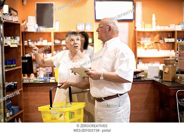 Senior couple with digital tablet in health shop