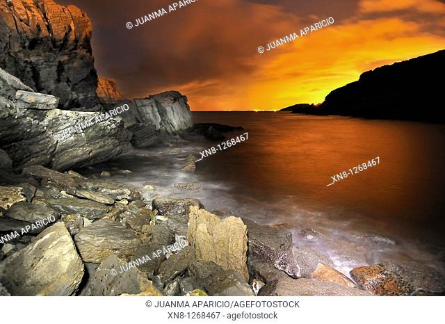 Night landscape of water and rocks photographed with long exposure time with a red sky orange background