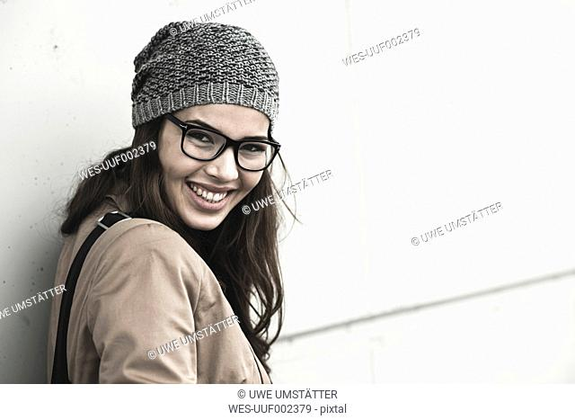 Portrait of smiling young woman wearing glasses and wool cap
