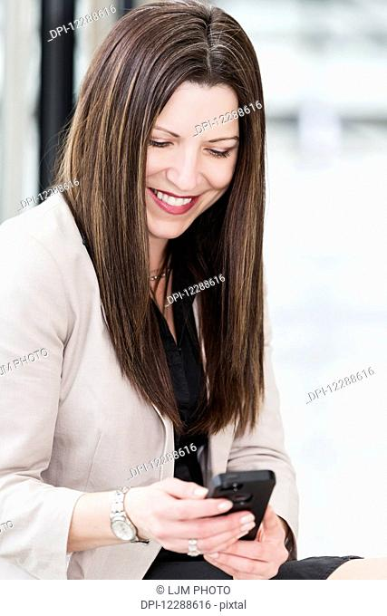 Mature business woman texting during a break from her work day; Edmonton, Alberta, Canada
