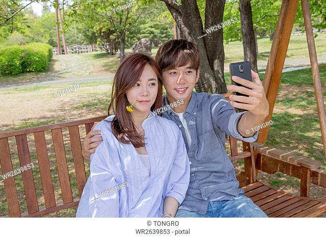 Young smiling couple having a date at park in spring