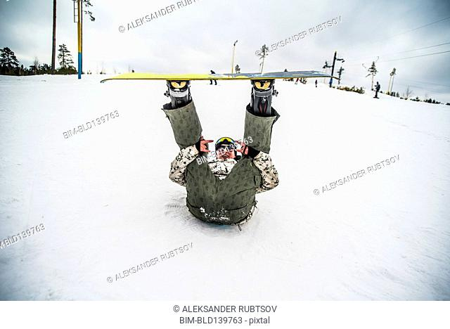 Caucasian snowboarder laying in snow with legs raised