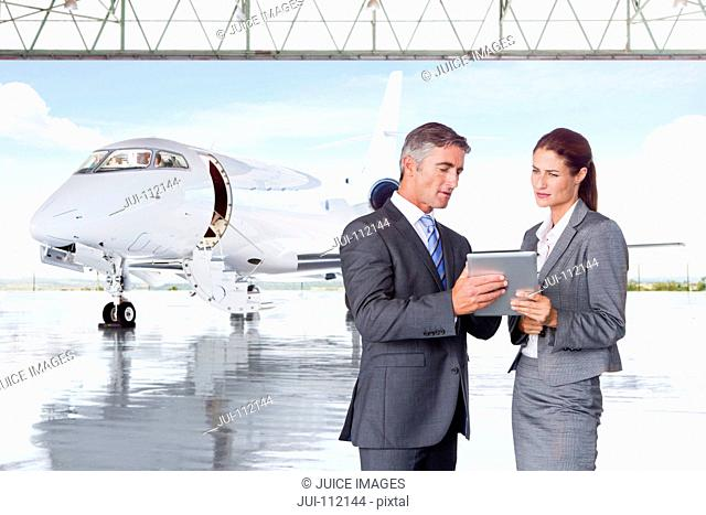 Businesswoman and Businessman with digital tablet discussing in front of private jet