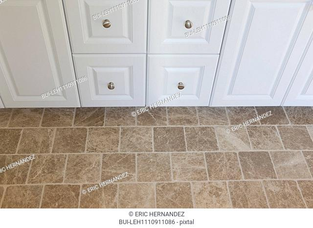 Close-up of drawer pulls and tiled floor at home
