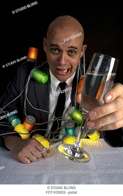 A drunk man with a string of lights around him holding a glass of champagne
