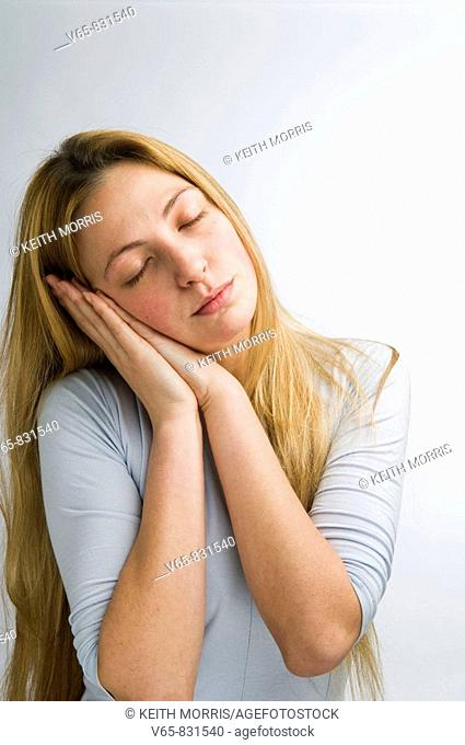 young woman resting her head in her hands as if about to go to sleep