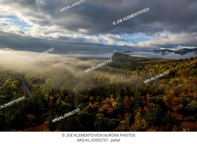 Early morning fog covering the bright fall foliage of New Hampshire as seen from Humphrey's Ledge in North Conway, New Hampshire