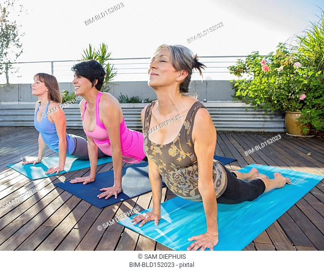 Women practicing yoga together on urban rooftop