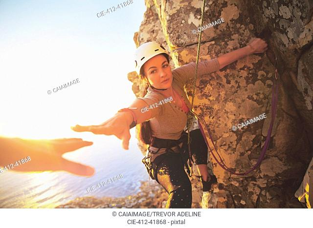 Female rock climber reaching for helping hand