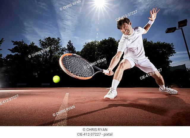 Young man playing tennis, reaching with tennis racket on clay court