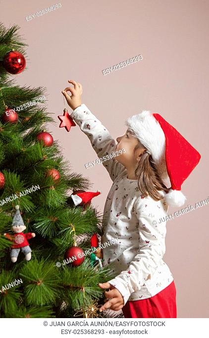 Little girl decorates Xmas Tree with red star