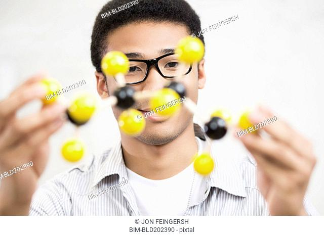 Mixed race teenager holding chemistry model