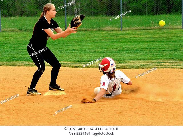 Runner sliding into base in a softball game