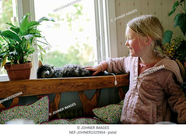 Girl stroking cat at home