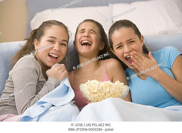 Sisters watching funny movie with popcorn