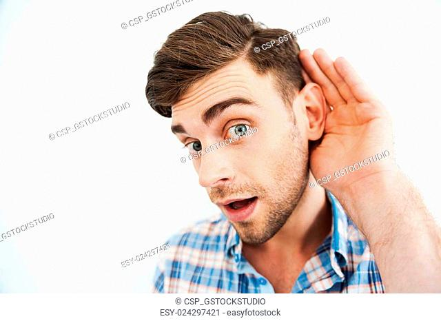 I want to know everything! Curious young man holding hand behind ear and looking at camera while standing against white background