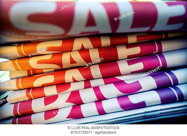 "Pile of folded newspapers with the text ""SALE"" in red and white. London, England"
