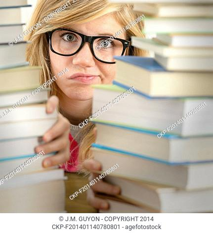 Desperate student teenager looking from behind stack of books library