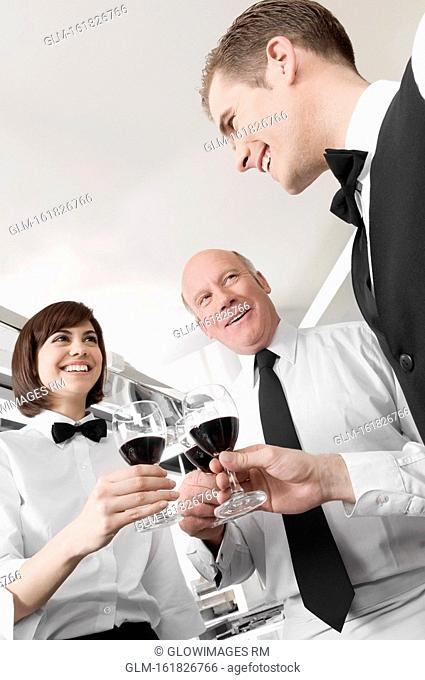 Two men and a woman toasting with wine