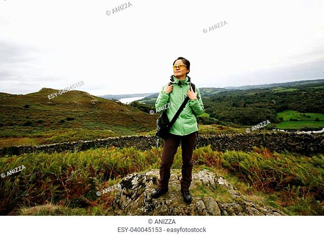 An East Asian Woman, stand on the lock, looking off into distance, hiking in Lake District, Cumbria, UK. Grasmere lake in the back ground