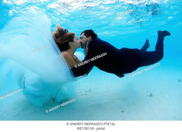 Newlyweds kissing under water, Indian Ocean, Maldives