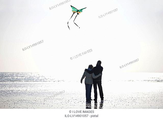A senior couple flying a kite on the beach, rear view