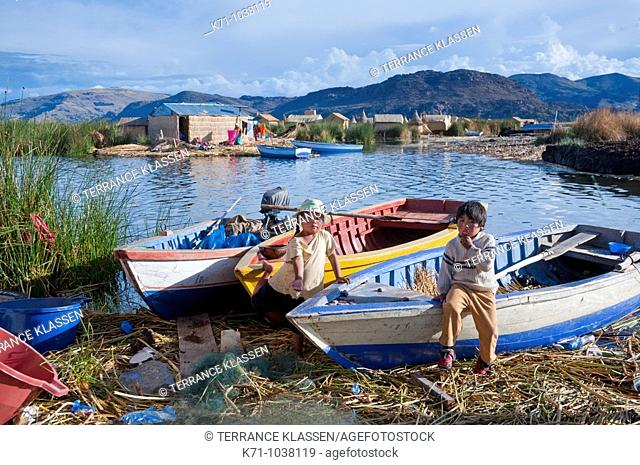 Children play near boats at the floating Islands in Lake Titicaca, Peru, South America