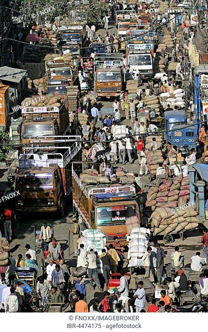 Merchants between trucks loaded with bags, Khari Baoli spice market, New Delhi, Delhi, India