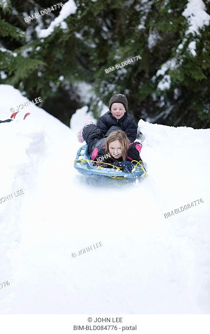Caucasian children sledding in snow