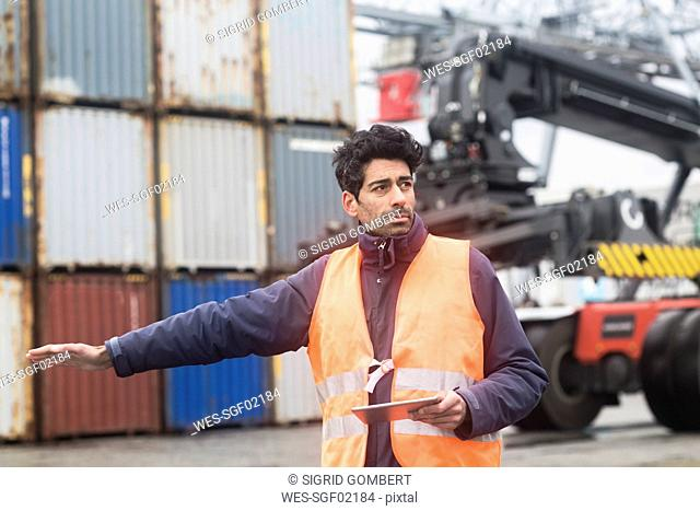 Man with tablet wearing reflective vest at container port