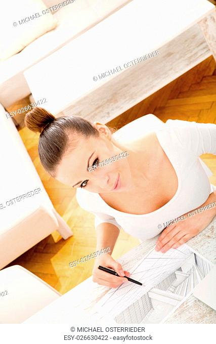 A young adult woman developing a architectural plan at home.