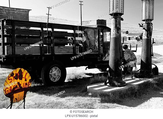 Desaturated image of gas station with antique truck parked at petrol pumps, with yellow original metal sign, Bodie pioneer village, California