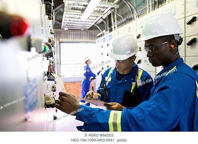 Male workers reviewing paperwork in gas plant