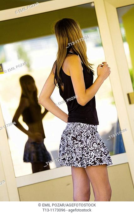 Posing before a reflective window young teenager girl