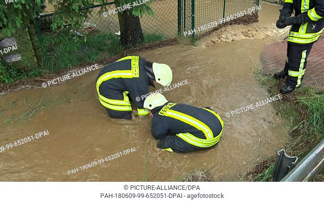 09 June 2018, Germany, Markneukirchen: Fire fighters work against the heavy rainfalls flooding local streets with water, mud and debris
