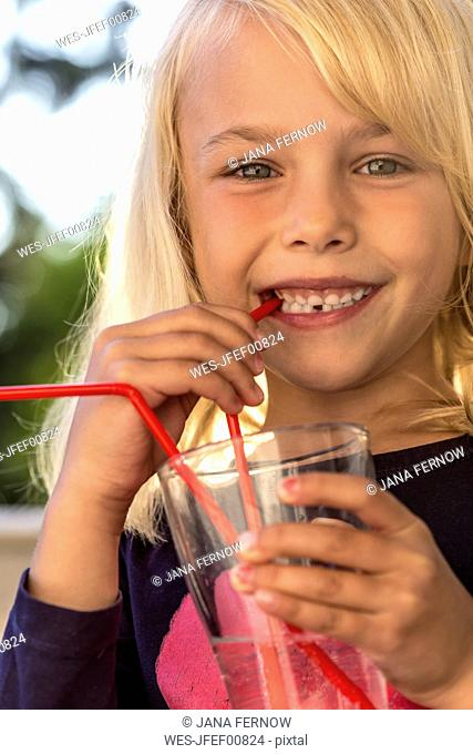 Little girl drinking water with drinking straw